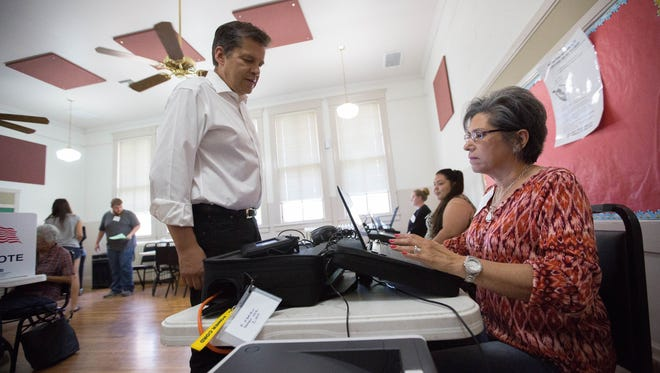 Joe Cervantes, one of the democratic candidates for governor of New Mexico, getting a ballot from Sylvia Calderon- Altamirano inside Frank O'Brien Paper Community Center, Tuesday June 5, 2018. Where Cervantes voted in the New Mexico primary election.