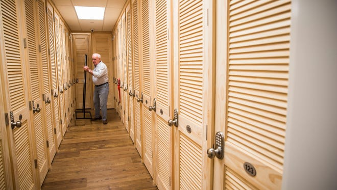 Bruce Nichols, owner of The Wine Store in Naples, Fla., moves a sign in the wine locker storage area on Wednesday, June 6, 2018.