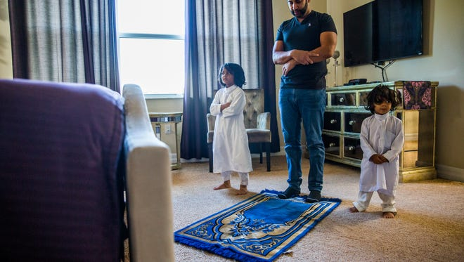 Javed Kapadia prays with his sons Ariz, 5, left, and Nyle, 2, in their Naples home on Wednesday, June 6, 2018.