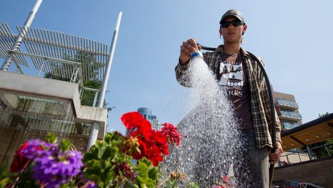 Alan Kissinger, a Cincinnati Parks employee, waters flowers in Smale Riverfront Park on Monday, June 18, 2018 in Cincinnati.