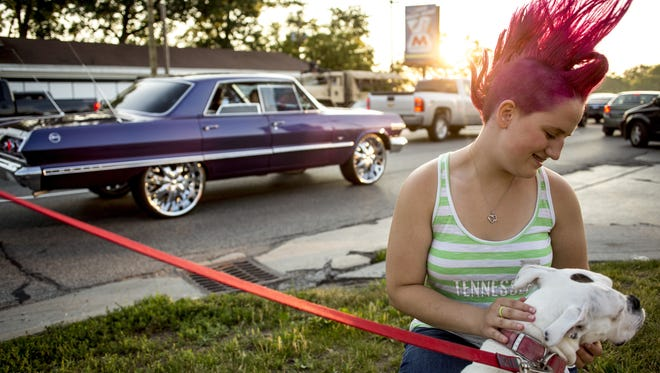 Sierra Tenniswood, then-14, of Port Huron, sports a pink mohawk and pets Princess as classic cars cruise by during Cruise Night Friday, June 24, 2016, on Pine Grove Avenue in Fort Gratiot.