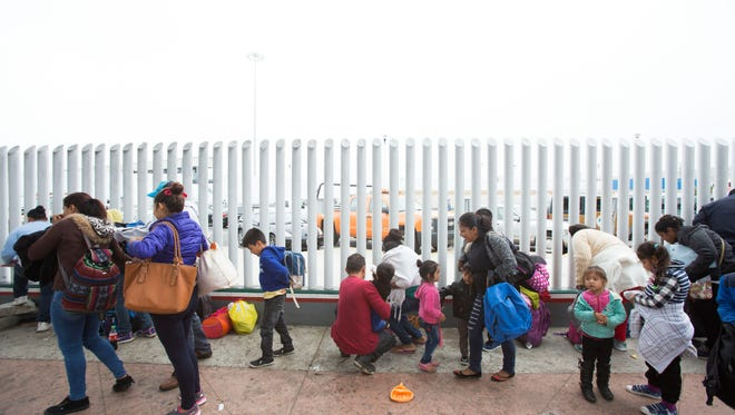 A group of 30 people made up of Mexican and Central American line up to enter the El Chaparral U.S. entry point in Tijuana with the intention of seeking asylum.