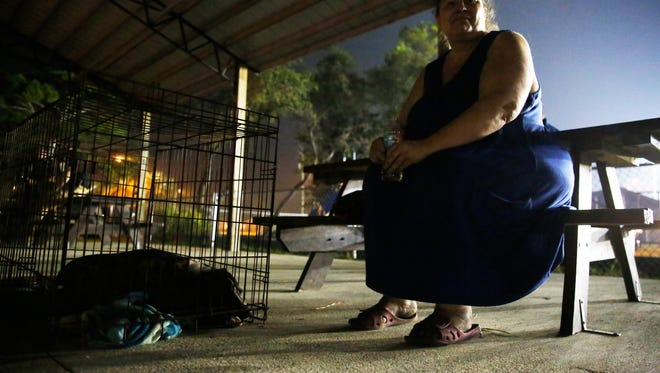 Barbra Fox, 48, sits with her roommate's dog Brownie at the East Point Volunteer Fire Department. A resident of East Point of 4 years, she and her roommate lived off on Ridge Road when the fire broke out on Sunday.