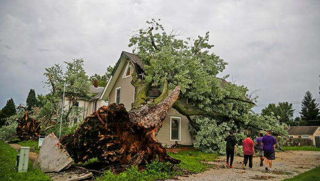 Neighbors survey the storm damage June 28 in Indianola. Two months after the storm officials are still working on clean up estimates.