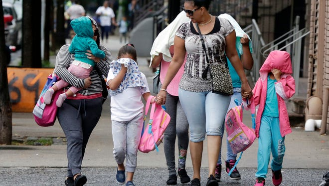 Two woman accompany immigrant children who had been separated from their parents Thursday, June 21, 2018 to the Cayuga Centers in New York.