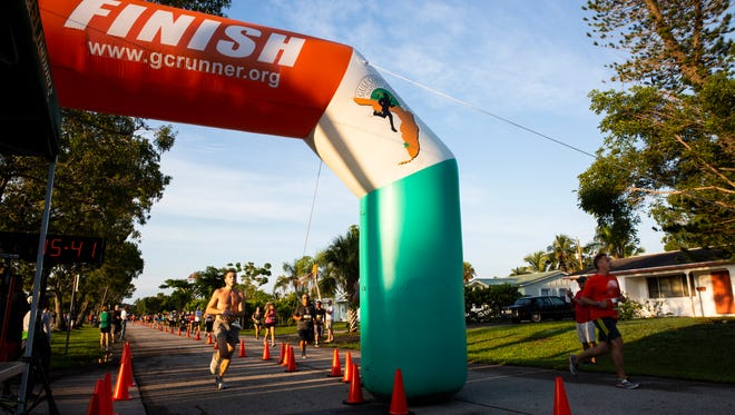 Joshua Wagner, 19, finishes first as other runners finish their first lap during the MoeÕs Firecracker 5k on July 4, 2018 at Fleischmann Park in Naples.