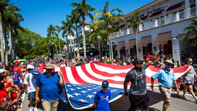 A giant American flag makes its way down Fifth Avenue South during the 4th of July Parade in downtown Naples on Wednesday, July 4, 2018.