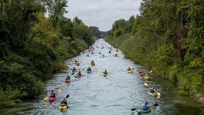 Hundreds of kayakers make their way up the Black River Canal during Paddle and Pour Saturday, August 27, 2016, in Port Huron.