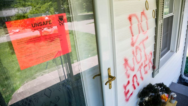 A sign marks a flood damaged home as unsafe to enter on East 35th street Monday, July 16, 2018.