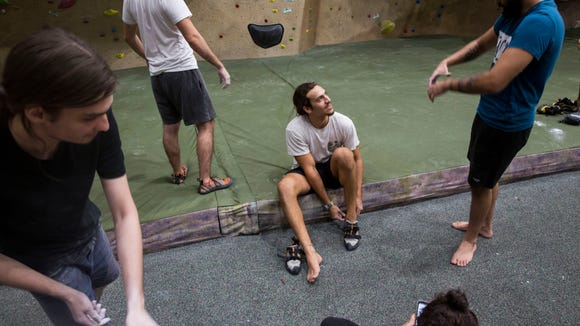 Alan Kellingley, from left, prepares to boulder, behind Robert di Rosa, while Niko Manheim, center, seeks advice from Rafael Hernandez on stretching out new climbing shoes at projectROCK in Oakland Park, Florida on Tuesday, July 17, 2018.