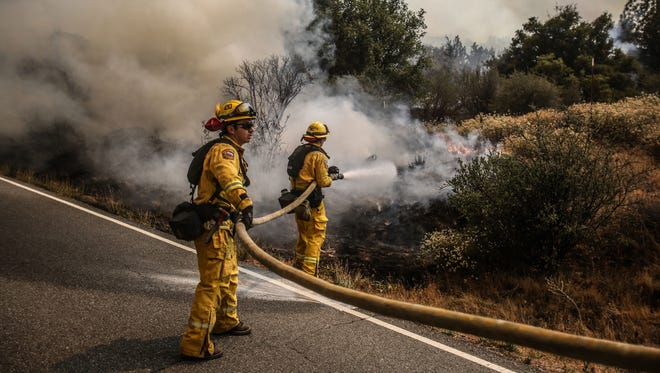 Fire fighters knock down hot spots along HWY 74 on Thursday, July 26, 2018 during the Cranston Fire.