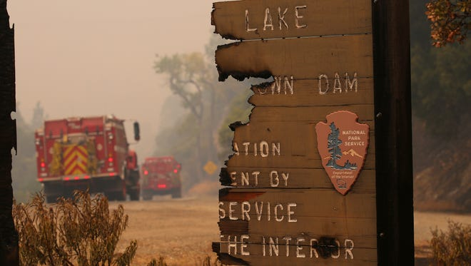 A National Park Service sign for Whiskeytown Lake and Dam is burned in two along Highway 299 in the Whiskeytown Shasta-Trinity National Recreation Area on Monday July 31, 2018 near Redding, CA. The area burned as a part of the Carr Fire.