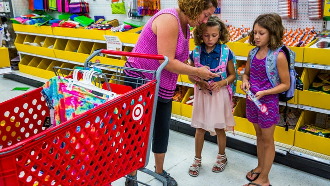 Tina Will of Naples shops for school supplies with her twin daughters Chaely, middle, and Cloey, both rising fourth graders, at Target in North Naples during the first day of the back to school tax holiday on Friday, Aug. 3, 2018. Families can shop for school supplies tax free through Sunday.