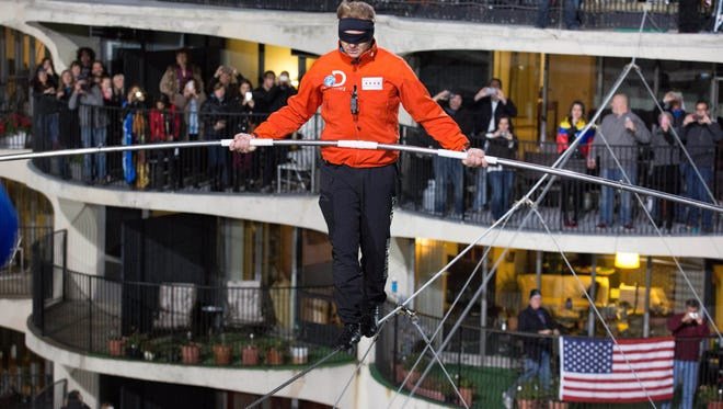 Nik Wallenda walks across the Chicago skyline blindfolded for Discovery Channel's Skyscraper Live with Nik Wallenda on Sunday, Nov. 2, 2014.