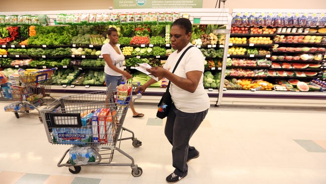 """Carolyn Newton, looks at her Kroger coupons as she shops at the Vine Street Kroger Monday morning. Newton said she doesn't think the Downtown area needs another grocery store. """"All they have to do is make this one larger, just expand it"""", Newton said. Photo shot Monday June 9, 2014. The Enquirer/Cara Owsley"""