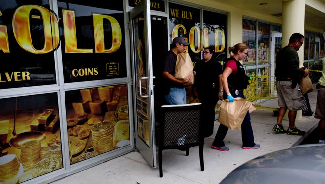 Members of the Cape Coral Police Department remove items from the Gold Store in Cape Coral.  The owner was arrested in what Cape Coral Police say is the largest fencing operation in Cape history.