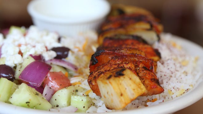 Chicken kabob plate served with side of cucumber salad at Kabobs Restaurant.