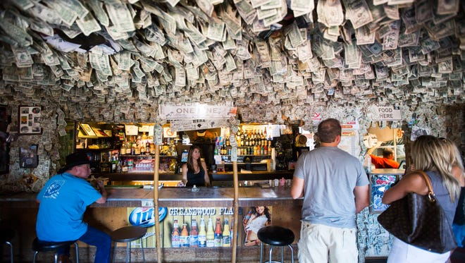People order from inside Greasewood Flat in the early afternoon in Scottsdale on Friday, Oct. 11, 2014. Dollar bills hang from the ceiling.