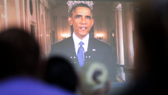 President Obama's image is put on a projected screen as he talks about his executive actions on immigration at Puente in Phoenix, AZ on Nov. 20, 2014.