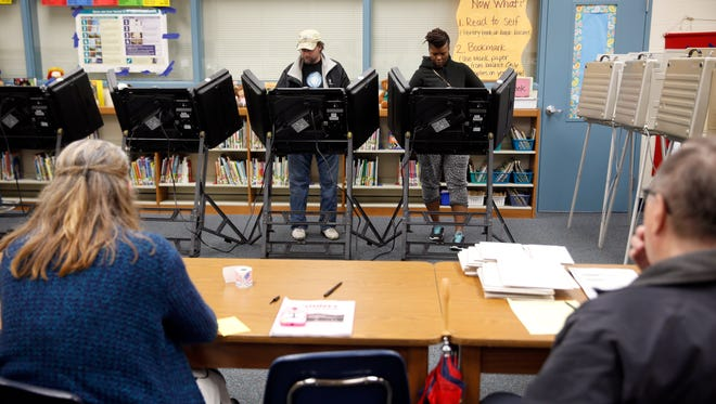 Rich Baranowski, second from left, and Tracy Hardy, second from right, vote as poll workers sit nearby during Ferguson's municipal election Tuesday, April 7, 2015, in Ferguson, Mo. Three of the six city council seats are up for grabs in the St. Louis County town where 18-year-old Michael Brown, who was black, was fatally shot by a white Ferguson police officer in August. (AP Photo/Jeff Roberson)