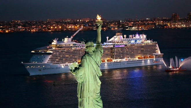 Royal Caribbean's Quantum of the Seas sails past the Statue of Liberty in New York Harbor.