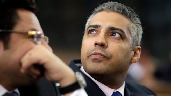 Al Jazeera journalist Mohamed Fahmy listens to his lawyer, Khaled Abou Bakr, during his retrial in Cairo on June 1, 2015.
