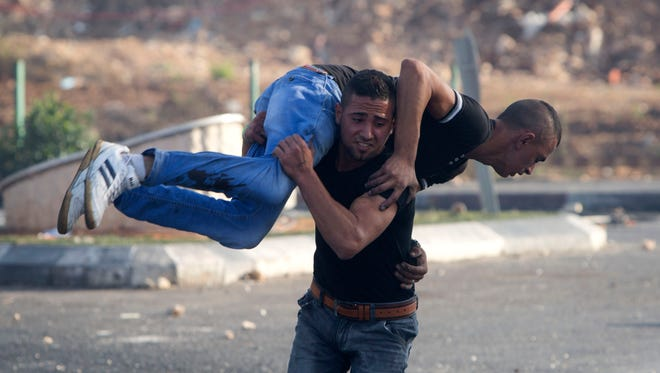 A Palestinian carries a man injured during clashes with Israeli troops near Ramallah, West Bank, on Oct. 8, 2015.