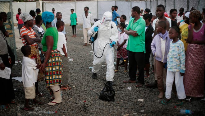 In this Sept. 30, 2014, photo, a  medical worker sprays people being discharged from the Island Clinic Ebola treatment center in Monrovia, Liberia.