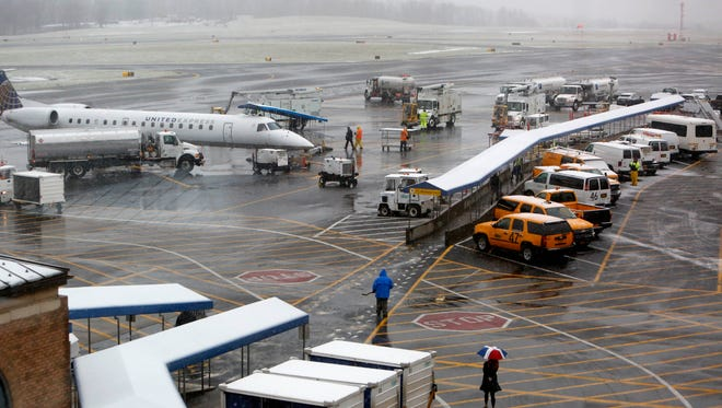 Passengers board a plane at Westchester County Airport, Nov. 26, 2014 in White Plains. A few flights were cancelled as snow begins to fall in the area on the day before Thanksgiving.