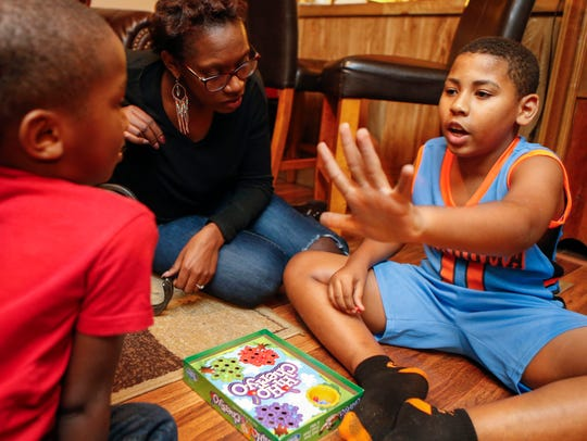 Ebony Dupont relaxes over a game with her sons, Bryson,