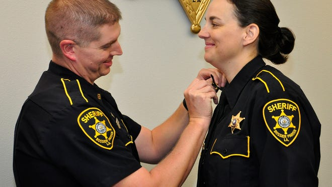 Bossier Deputy Ryan Rhodes pins lieutenant's bars on the collar of his wife, Lt. Sarah Rhodes, who will now serve as supervisor of academy operations at the North Louisiana Criminal Justice Academy, which is the Bossier Sheriff's Office Training Division.