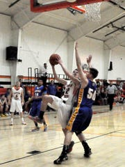 Capitan's Brendon Carter goes for the layup as Mesilla Valley's Dalton Rice attempts the block.
