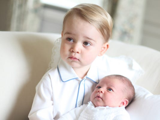 Princess Charlotte, right, being held by her brother, 2-year-old, Prince George
