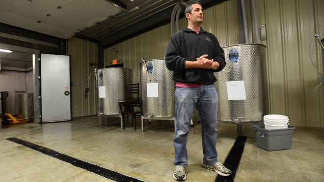 Hocking Hills Winery CEO Blaine Davidson stands in front of vats of white wine Wednesdayin Logan. The winery opened to the public on April 4.