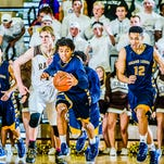 Malek Adams, center, had 18 points in Grand Ledge's victory over rival Holt.