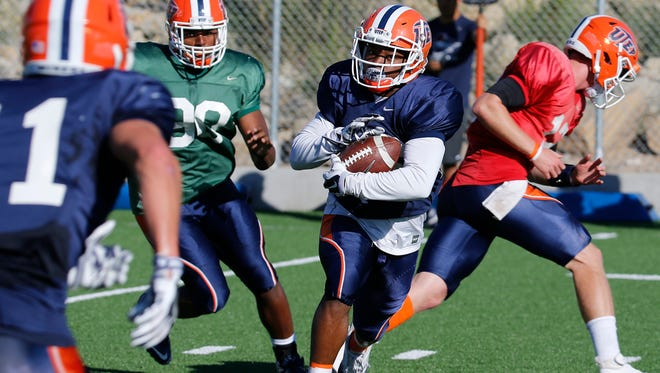 UTEP receiver Walter Dawn (26) takes the ball from UTEP quarterback Ryan Meitz, on an end around play during practice Wednesday morning at Glory Field. The Miners are preparing for thier homecoming game opponent Old Dominion Saturday night in the Sun Bowl.
