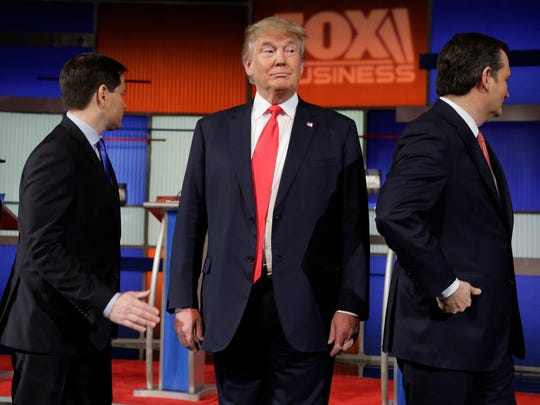 Donald Trump stands on the stage before the Fox Business