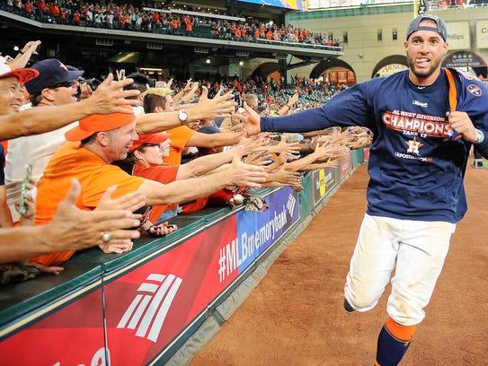 Houston Astros' George Springer celebrates with fans