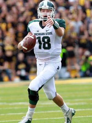 Michigan State quarterback Connor Cook looks to pass against the Iowa Hawkeyes at Kinnick Stadium.