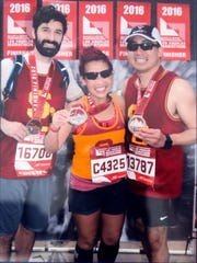 Kathy Nguyen is pictured with her husband, Robby Alvarez (right) and Jonathan Russin, the doctor who performed brain surgery on her less than a year prior, after they all completed the Los Angeles marathon. The photo is displayed with other racing mementoes in her family's Newark home.