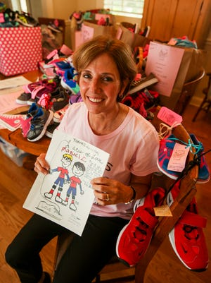 Jeanne Nealon is co-founder and president of Laces of Love, holds some of the thank you letters the group gets from the children after they deliver the shoes. Laces of Love is a charity that provides new shoes for low income and disadvantaged children in Lee and Collier counties. Since 2005, the charity has served provided more than 80,000 children with a new pair of shoes.