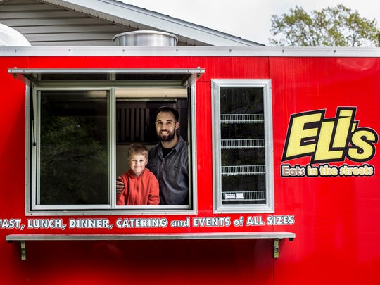 "Gary Lokers, of Kimball Township, pictured with his son, Eli, 4, on his new food truck called ""Eli's Eats."""