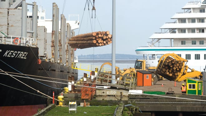 Logs are lifted by crane onto a cargo ship at the Port of Astoria in 2011.