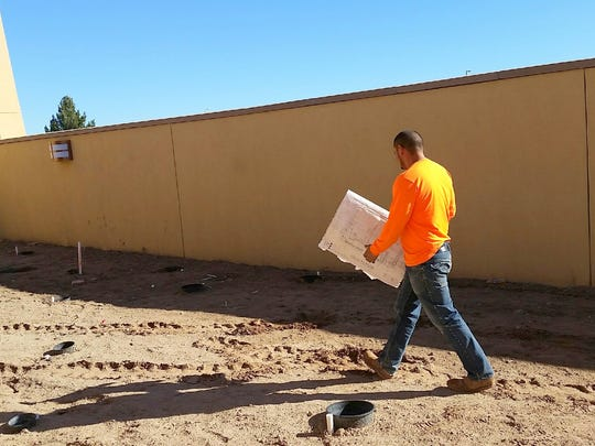 Frank Silva, a landscaping contractor, examines plans at the new Mesilla Valley Regional Dispatch Authority building, located north of the County Government Center off Motel Boulevard in Las Cruces. Landscaping is one of a few remaining chores that must be finished as part of the $8.25 million construction project.