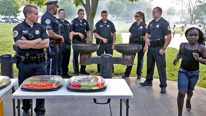 A group of Des Moines police officers chatted as they attended the annual Safe Summer Kickoff event held at Evelyn Davis Park on Forest Ave. in Des Moines on May 29, 2014.