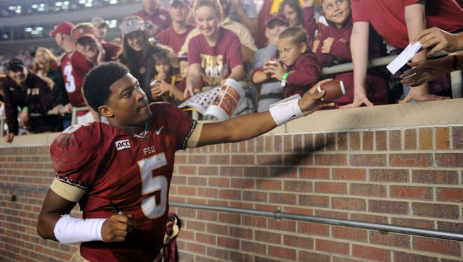 Florida State Seminoles quarterback Jameis Winston (5) signs autographs for fans after the game against the Idaho Vandals at Doak Campbell Stadium.