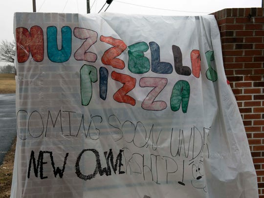 Nuzzella's Pizza has a temporary sign for the new business