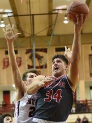 West Side's George Karlaftis drives hard to the basket