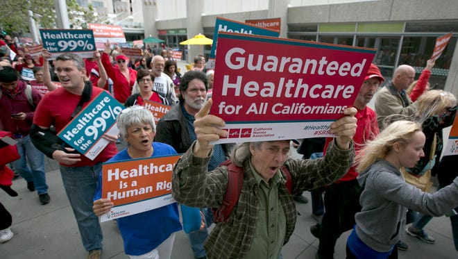 In this April 26, 2017 file photo supporters of single-payer health care march to the Capitol in Sacramento, Calif. The state Senate approved, SB562 by Democratic State Senators Ricardo Lara, of Bell Gardens, and Toni Atkins, of San Diego, that would guarantee health coverage with no out-of-pocket cost for all California residents, including people living in the country illegally.