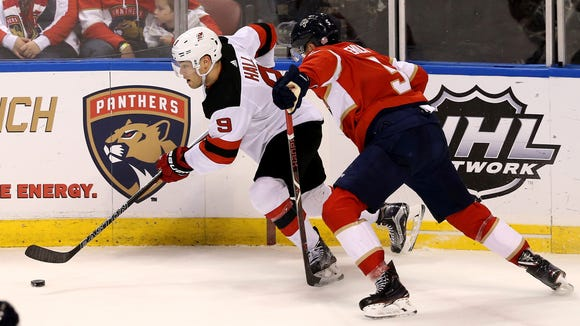 New Jersey Devils left wing Taylor Hall (9) controls the puck as Florida Panthers defenseman Aaron Ekblad (5) defends in the first period at BB&T Center.